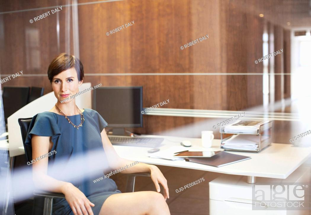 Stock Photo: Portrait of confident businesswoman sitting at desk in office.