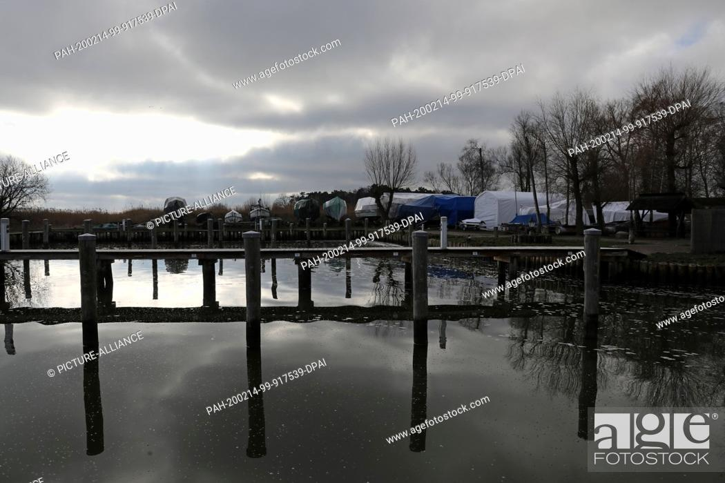 Stock Photo: 14 February 2020, Mecklenburg-Western Pomerania, Dierhagen: In the water of the Bodden harbour the dark clouds are reflected.