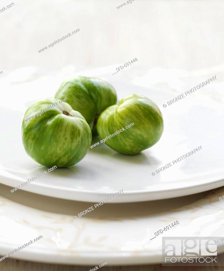 Photo de stock: Three Green Heirloom Tomatoes on a White Plate.