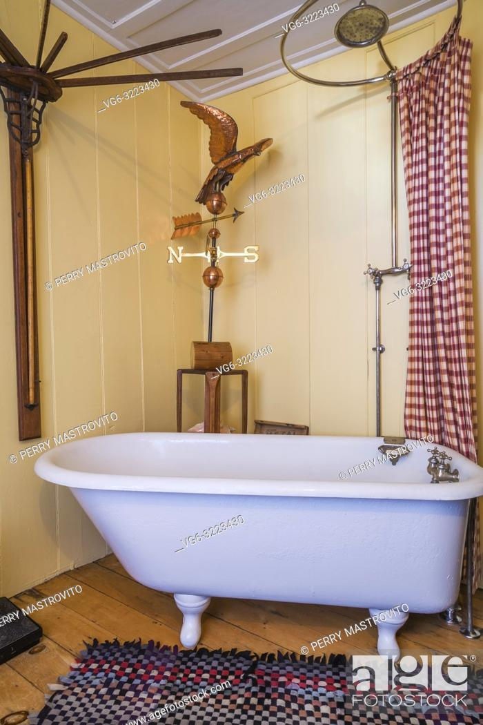 Imagen: Freestanding clawfoot bathtub in main bathroom with yellow walls on ground floor inside an old 1835 fieldstone house.
