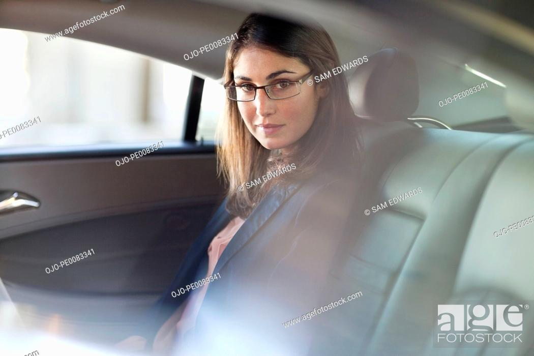 Stock Photo: Portrait of confident businesswoman in back seat of car.