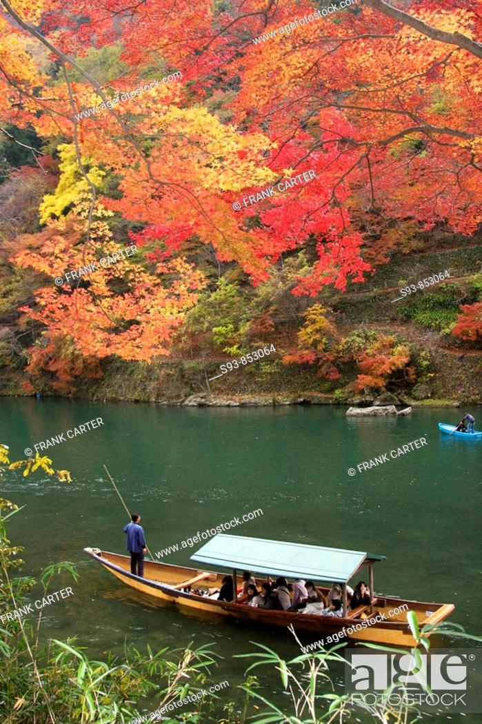 Stock Photo: A pleasure boat being poled along the pond in Arashiyama under red-orange autumn maple leaves.