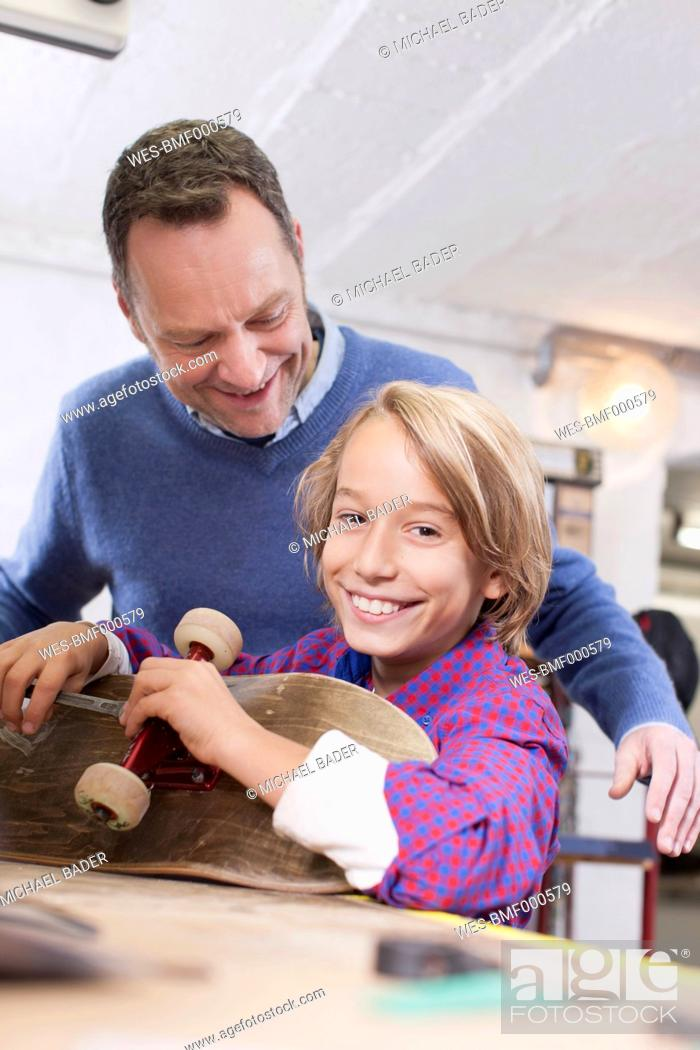Stock Photo: Germany, Leipzig, Father and son repairing skateboard.