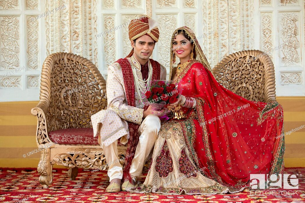 d3e3e6048e Stock Photo - Indian bride and groom in traditional wedding dress sitting  on a couch