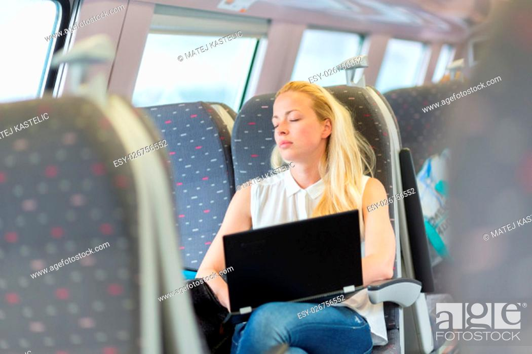 Imagen: Businesswoman naping sitted while traveling by train and working on laptop. Tiresome business travel.
