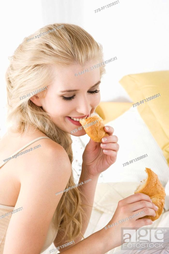 Stock Photo: Woman eating croissant in bed.