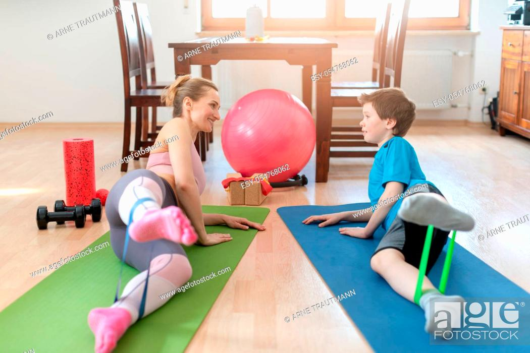 Stock Photo: Family doing sport exercises at home during Covid-19 lockdown training the legs with resistance bands.