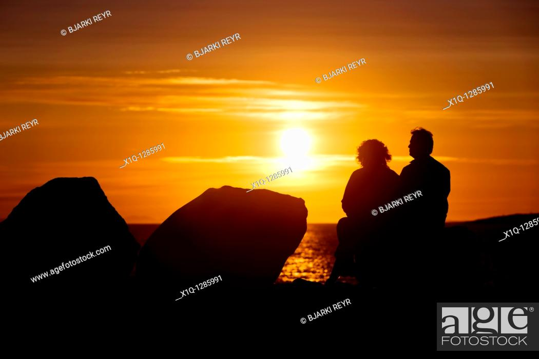 Stock Photo: People sitting and enjoying the midnight sun setting over the Atlantic Ocean  Reykjavik Iceland.