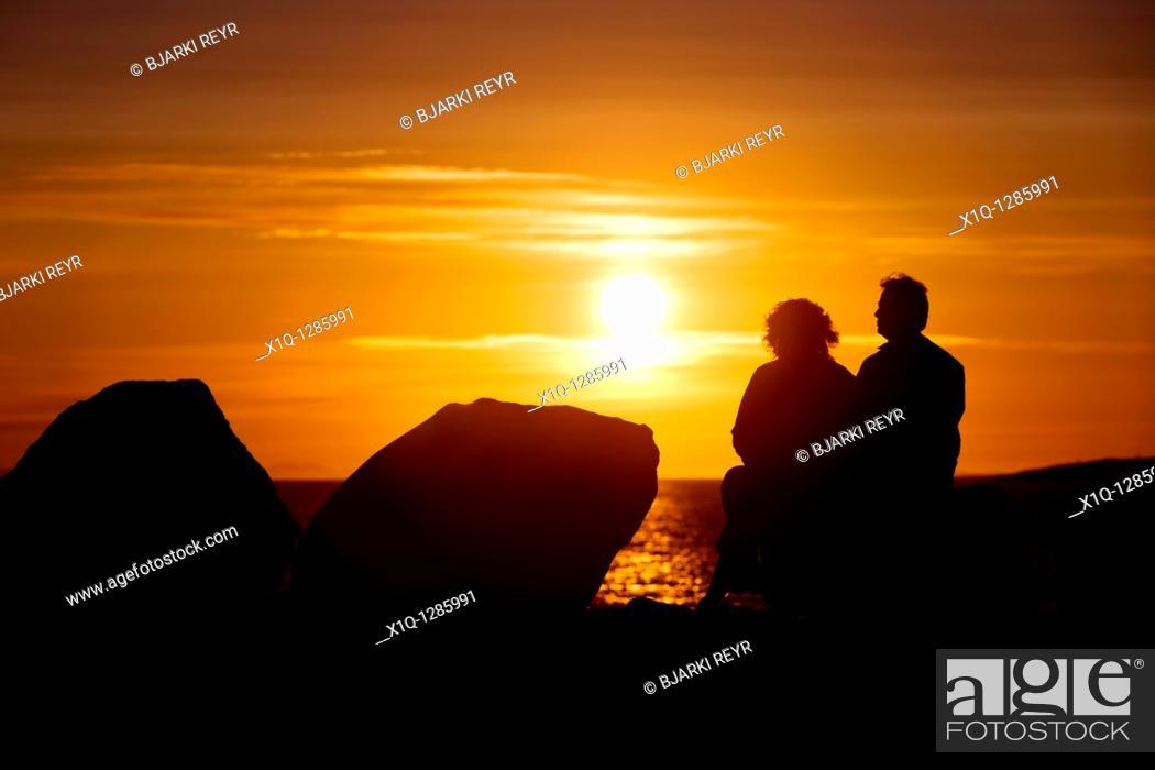 Stock Photo: People sitting and enjoying the midnight sun setting over the Atlantic Ocean  Reykjavik Iceland.