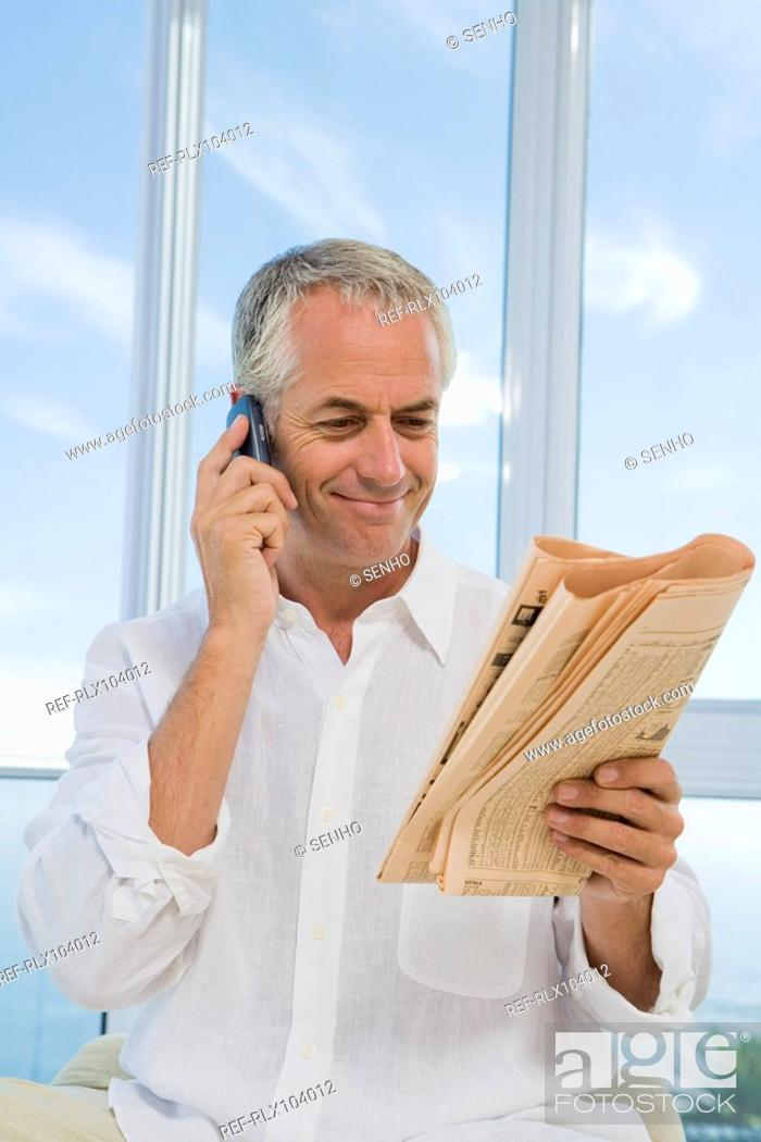 Stock Photo: Mature man smiling, using Cell phone and reading financial newspaper.