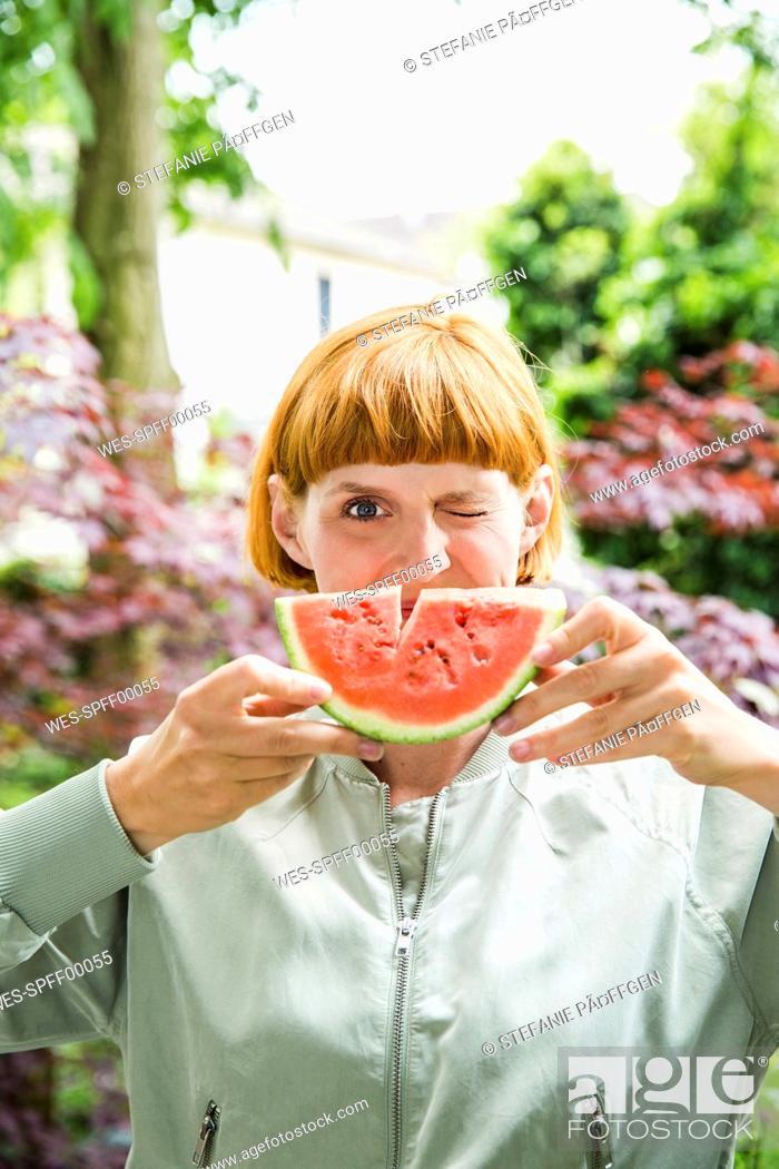 Stock Photo: Portrait of winking woman holding slice of watermelon.