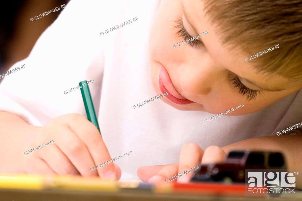 Stock Photo: Close-up of a boy drawing on a sheet of paper.