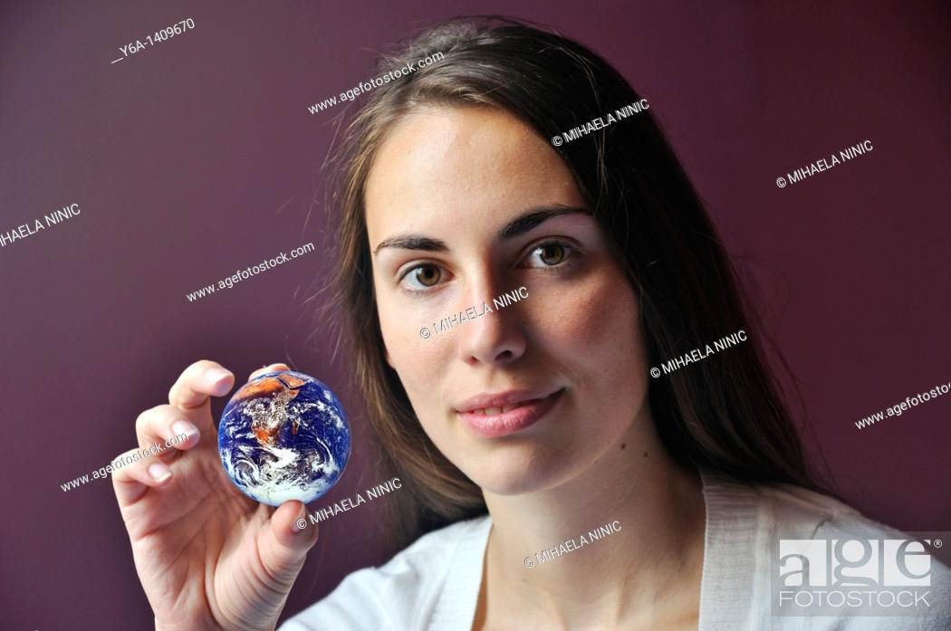 Stock Photo: Young woman holding planet earth.