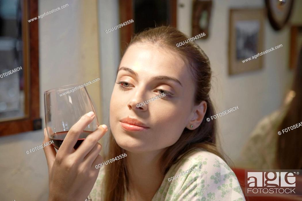 Stock Photo: Young woman drinking red wine (portrait).