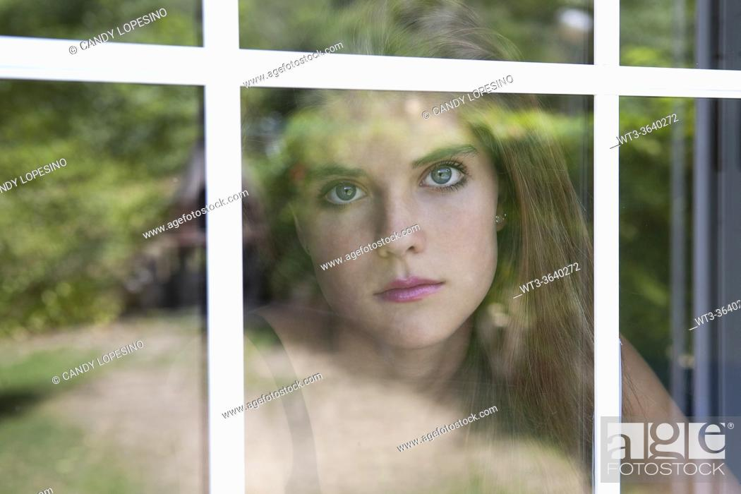 Stock Photo: Portrait of teenage girl behind the window, reflections of vegetation in the glass.