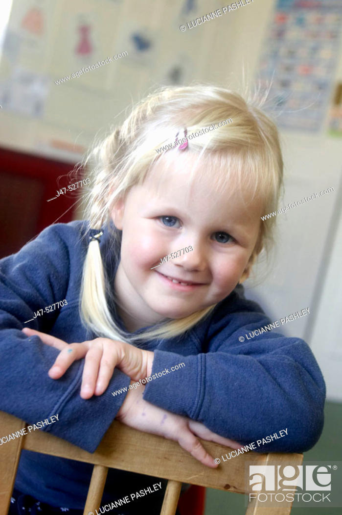 Stock Photo: 3 year old girl smiling into camera at nursery.