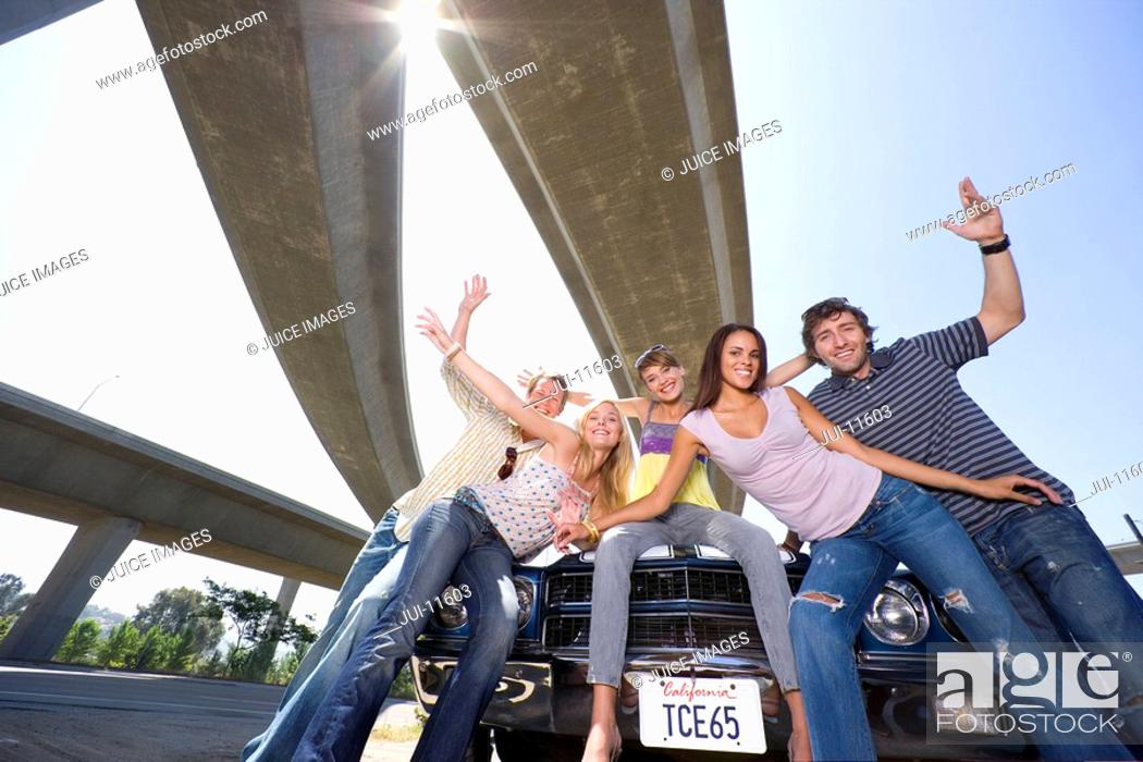 Stock Photo: Medium group of friends on bonnet of car beneath overpass, smiling, portrait, low angle view sun flare.