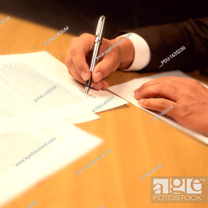 Stock Photo: close-up of a mans hand signing on a document.