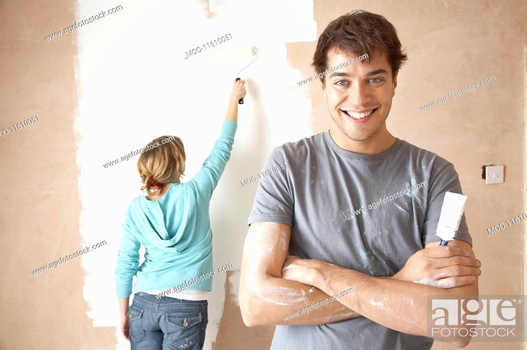 Stock Photo: Couple painting interior wall using brush and roller.