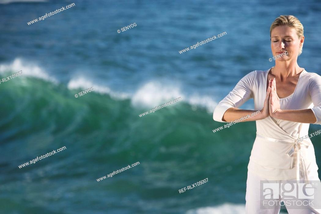 Stock Photo: Mature woman standing in prayer position, with waves breaking in background.