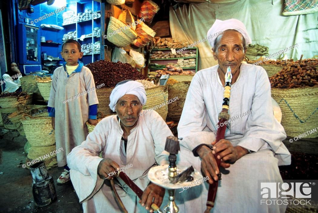 Stock Photo: two men smoking hookah in front of their shop, Aswan, Egypt, Africa.