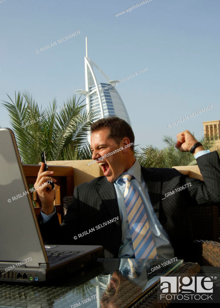 Stock Photo: Triumphing businessman with mobile phone in Dubai (Burj Al Arab hotel in background).
