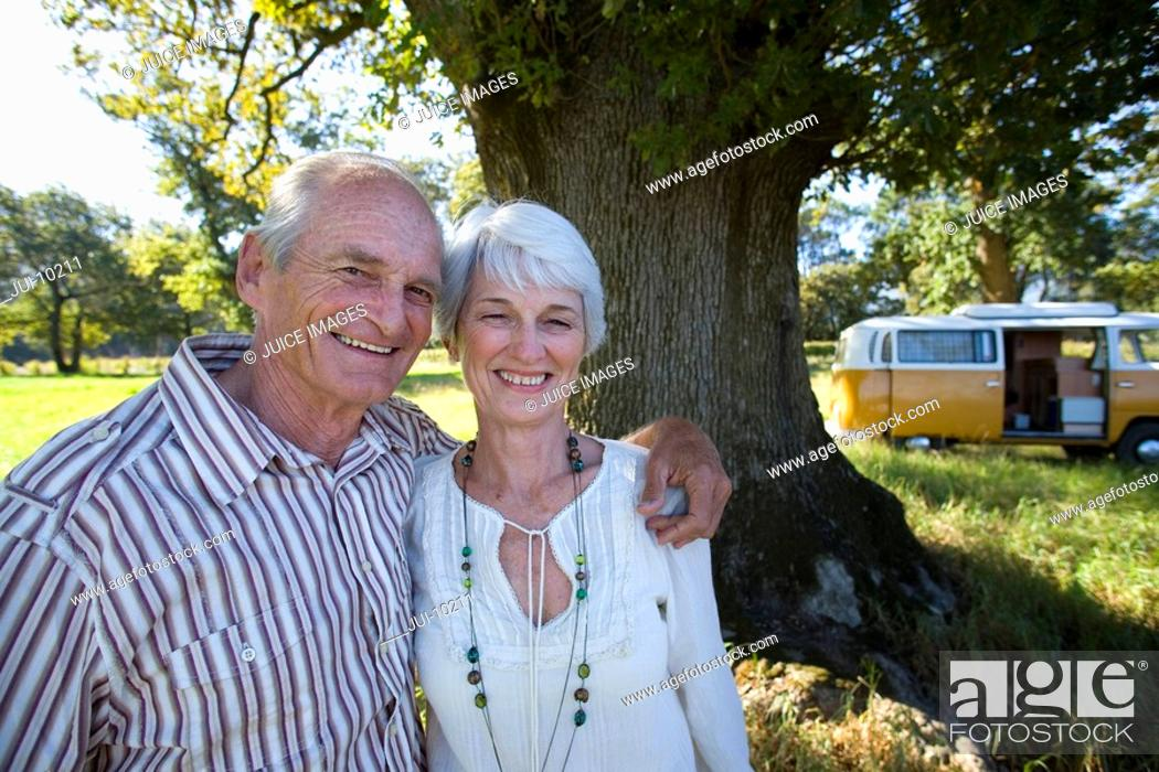 Stock Photo: Senior couple arm in arm in field, camper van in background, smiling, portrait.