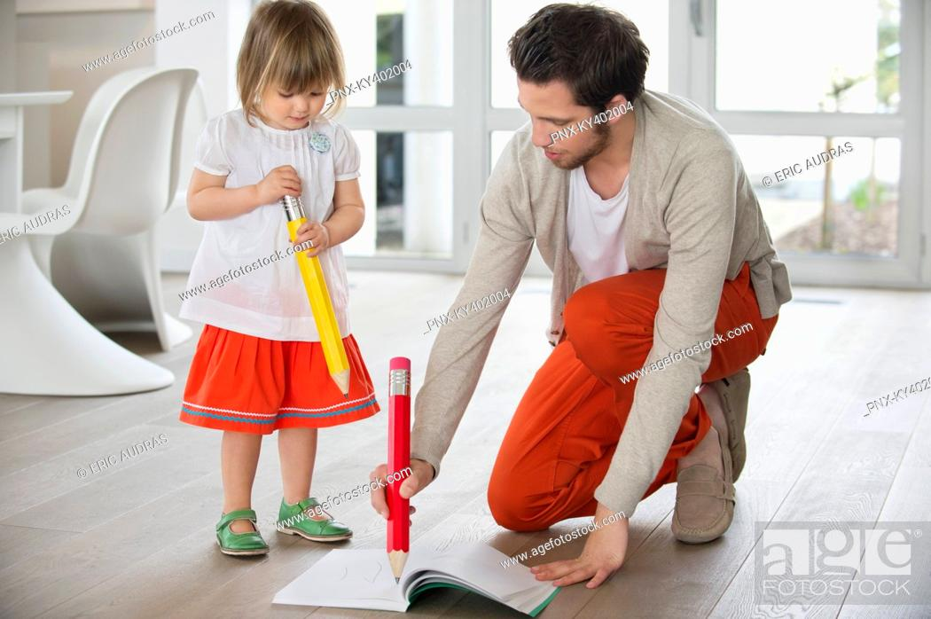 Stock Photo: Man and daughter writing with big pencils.