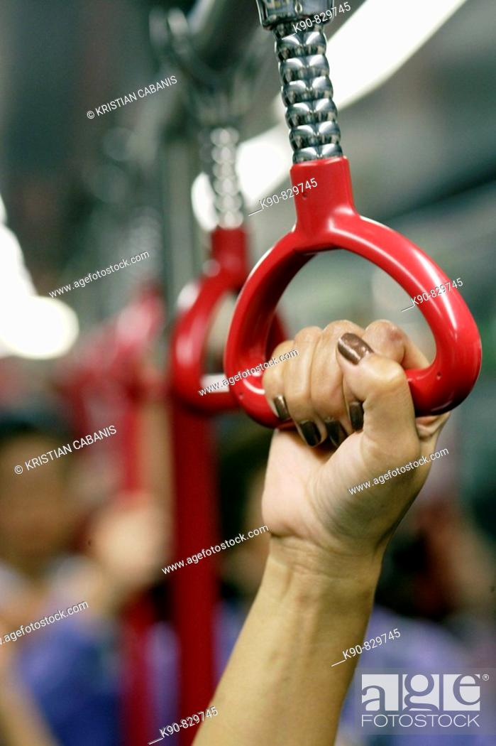 Stock Photo: Hand of an Asian woman holding the grip in the underground, Hong Kong, China, Southeast Asia.