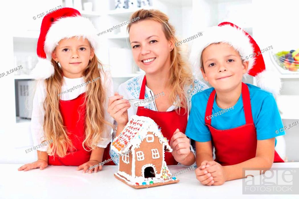 Imagen: Family at christmas making a gingerbread cookie house.