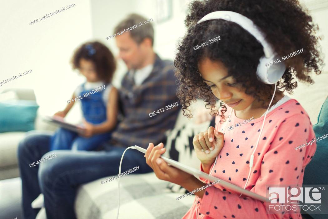 Stock Photo: Girl with headphones using digital tablet on sofa.