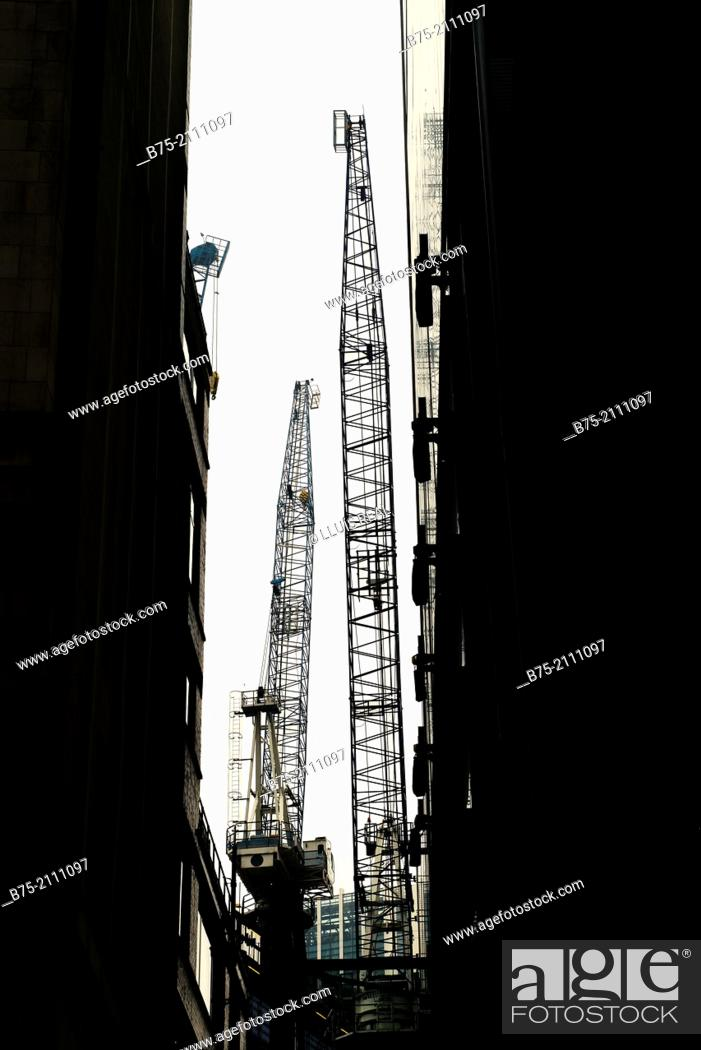 Stock Photo: Two cranes on a construction building overlooking between two office buildings in the City of London, England, UK, Europe.