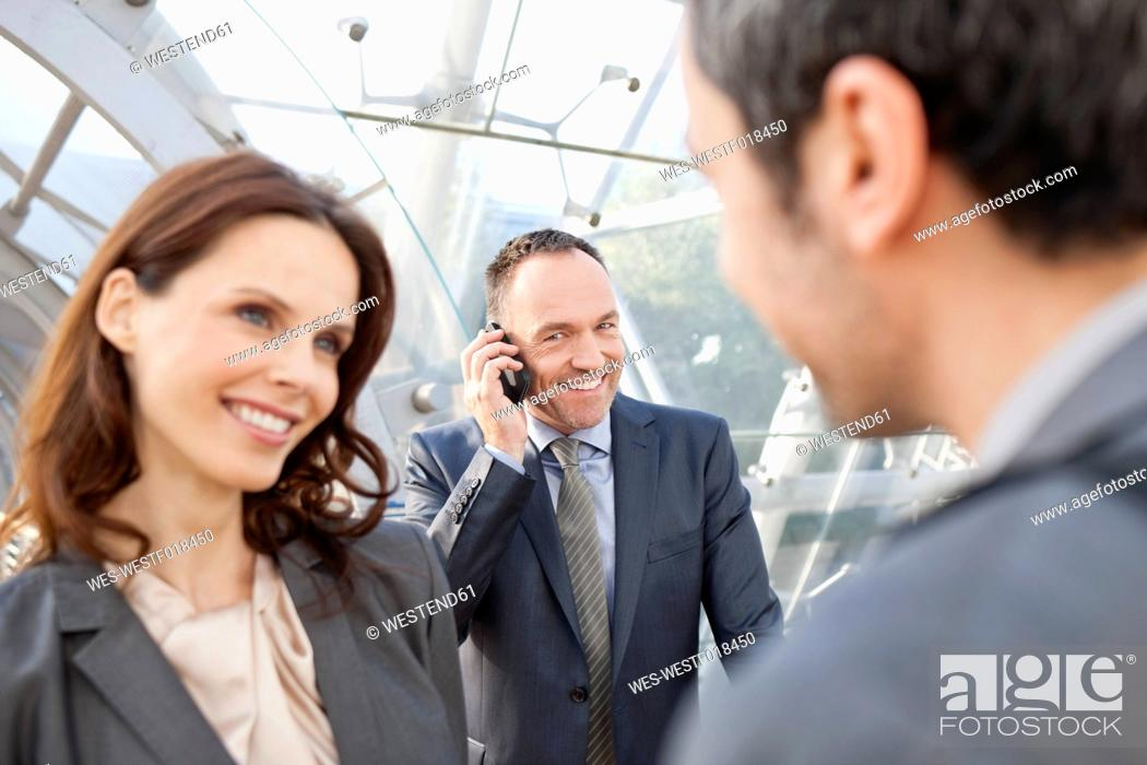Stock Photo: Germany, Leipzig, Business people smiling, businessman with cell phone in background.