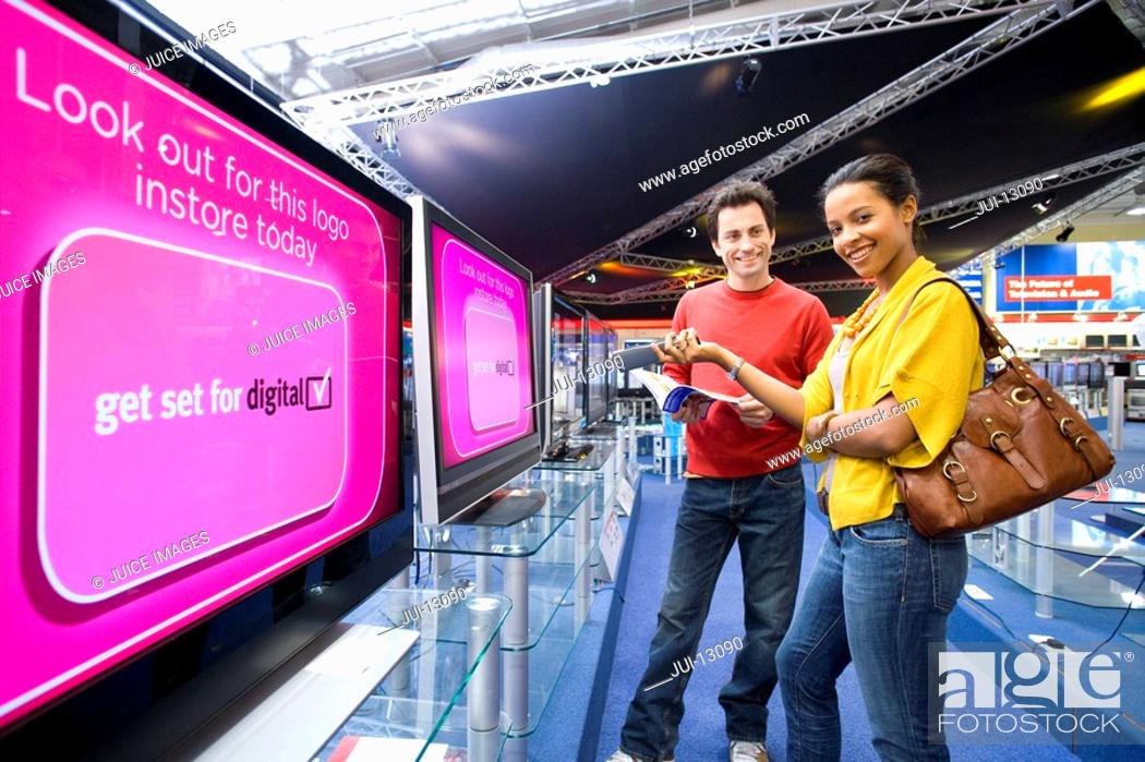 Stock Photo: Young couple shopping for television, smiling, low angle view.