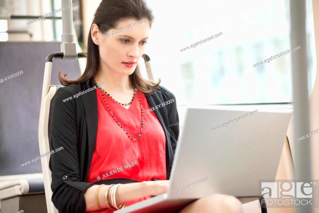Stock Photo: Woman traveling in a bus and using a laptop.