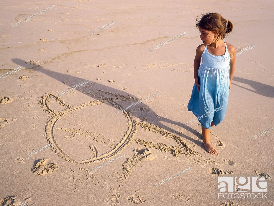 Stock Photo: Six-year-old girl in a blue dress and a drawing of a fish in the sand on the beach one summer afternoon.