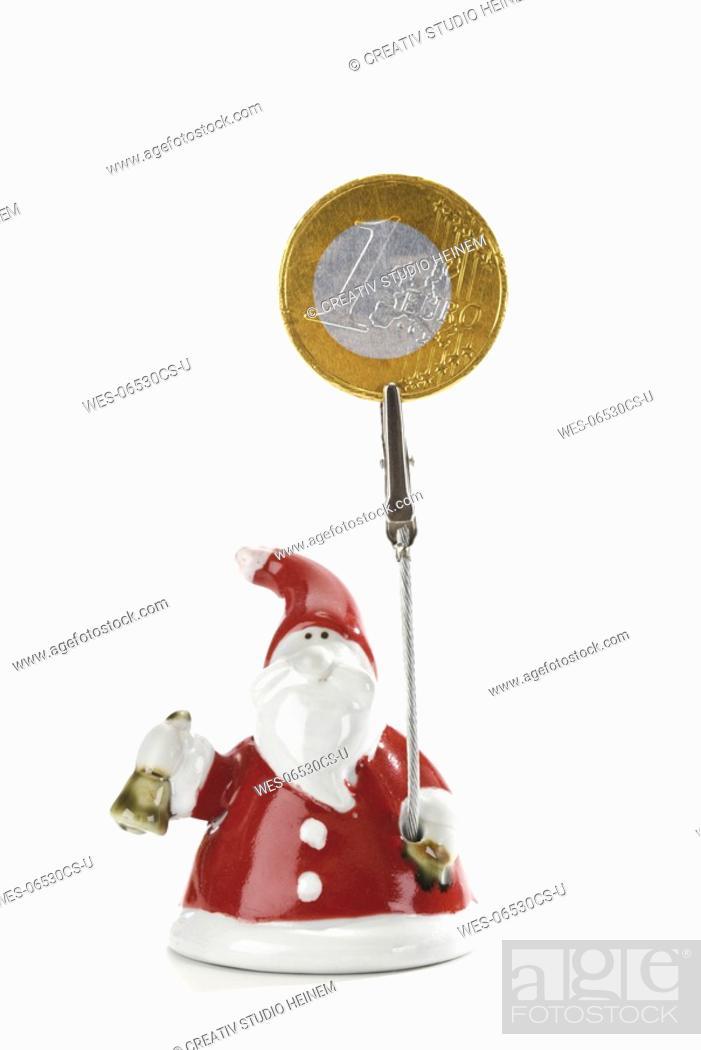 Stock Photo: Santa Claus Figurine holding Euro coin.