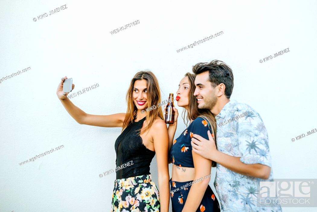 Stock Photo: Friends taking a selfie with smartphone in front of white wall.
