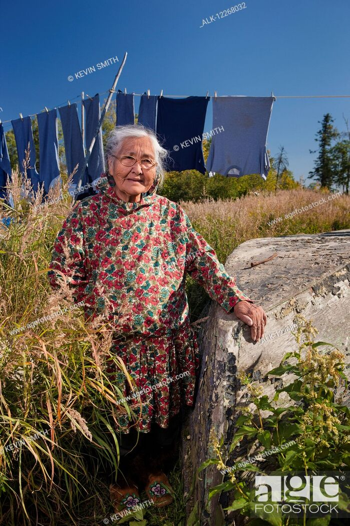 Imagen: Female Alaskan native elder wearing a kuspuk posed next to an old boat with a clothesline in the background, Shungnak, Alaska, summer.