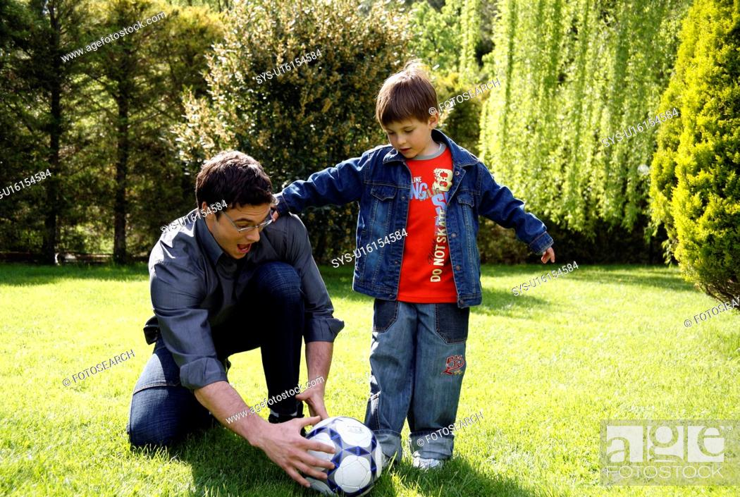 Stock Photo: Man teaching boy to play soccer.