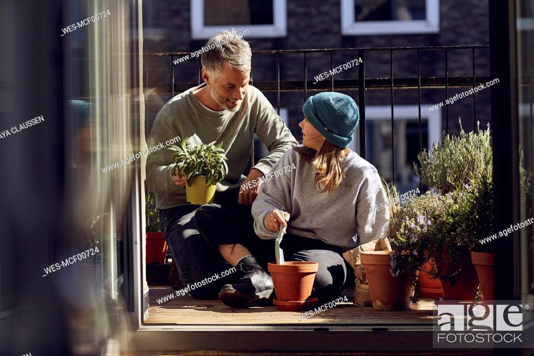 Stock Photo: Father and daughter planting together on balcony.