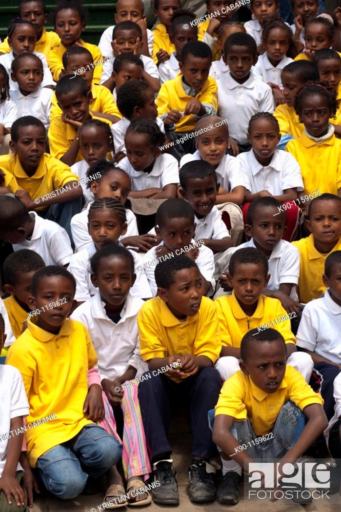 School class with young girls and boys in yellow and white
