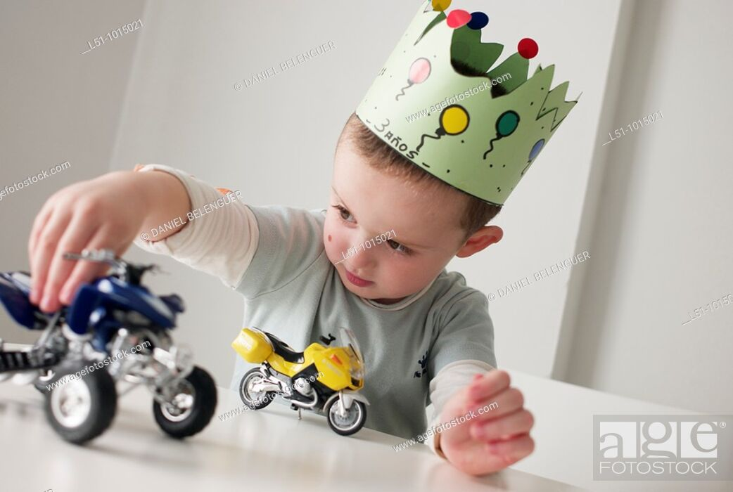 Stock Photo: Boy with a crown in his birthday playing with cars on a table.