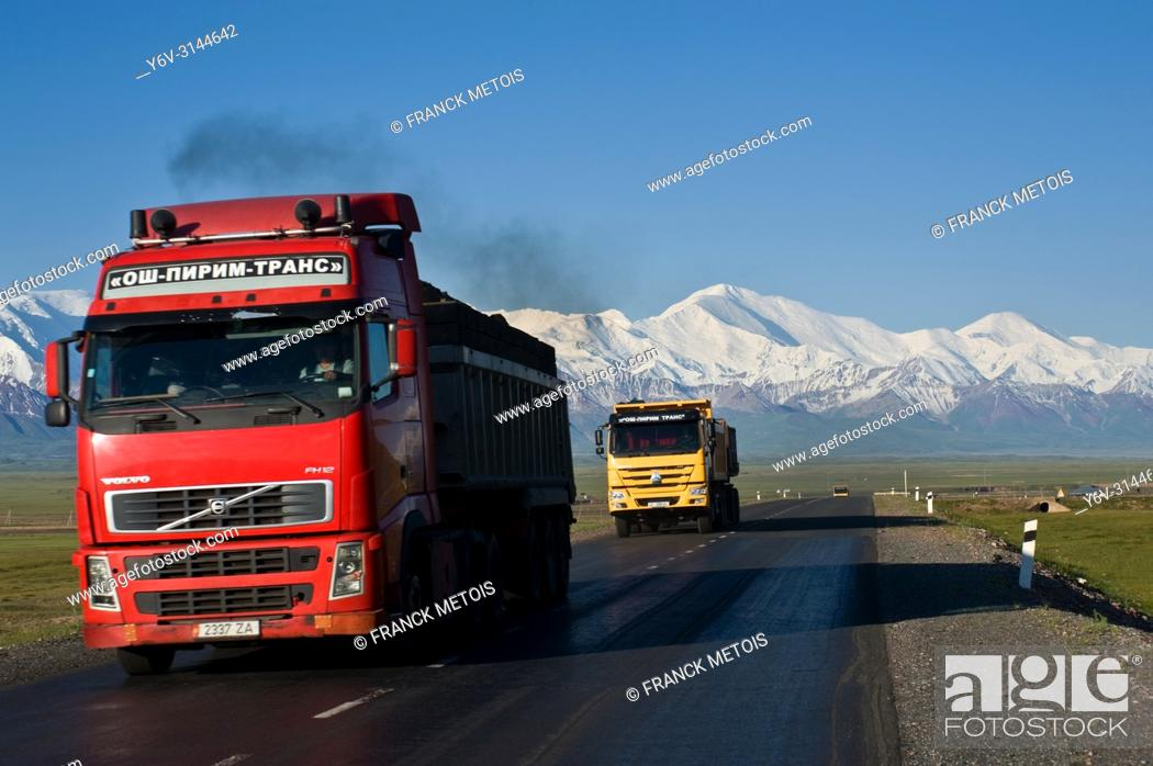 Stock Photo: Trucks carrying coal to China on the Pamir highway ( Alay valley, Kyrgyzstan). In the background, peak Lenin ( 7134 mts) is visible.