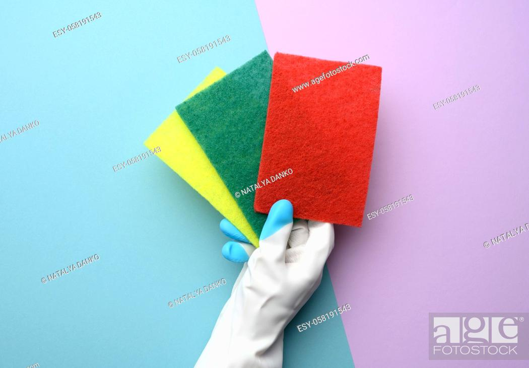 Stock Photo: female hand in a white rubber glove holds multi-colored kitchen sponges on a purple background, close up.