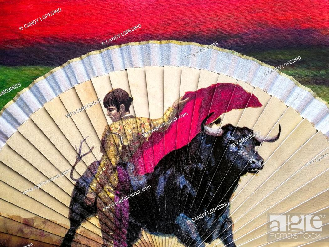 Stock Photo: Bullfighting scene on a hand fan on red background.