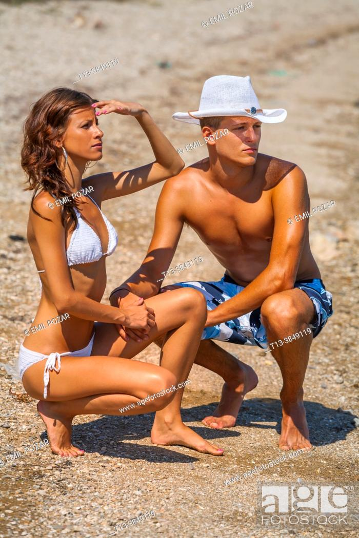 Imagen: Muscular boy slender girl young couple on the beach are looking away.