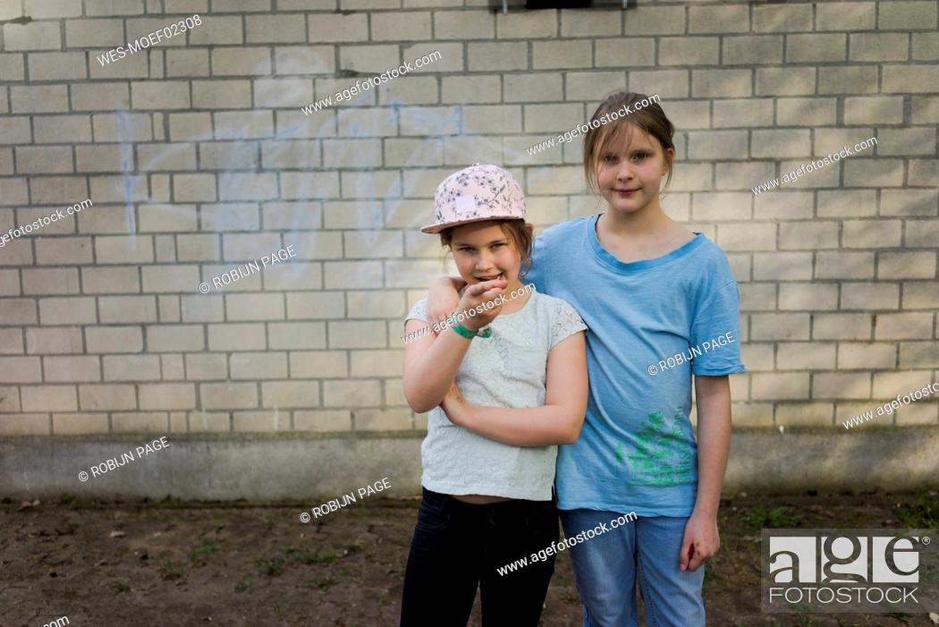 Stock Photo: Portrait of two girls standing in front of a brick wall.