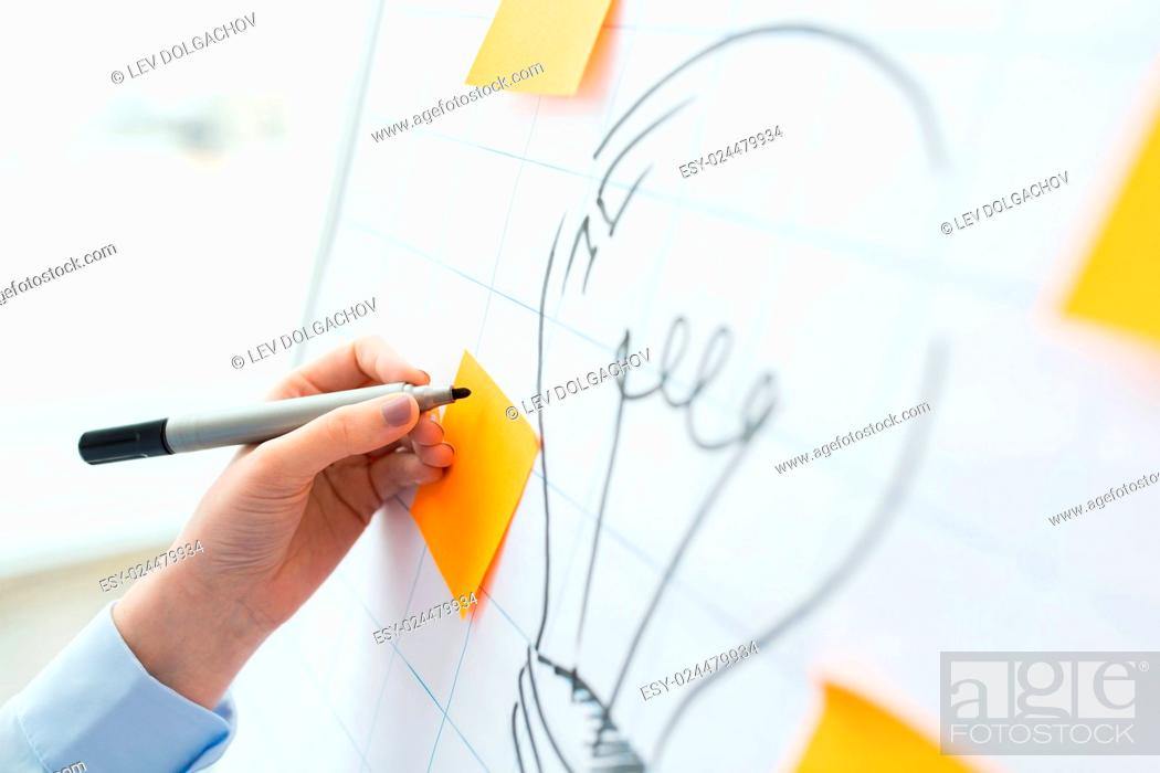 Stock Photo: business, people, idea, startup and education concept - close up of hand with marker drawing light bulb or writing to sticker on flip chart at office.