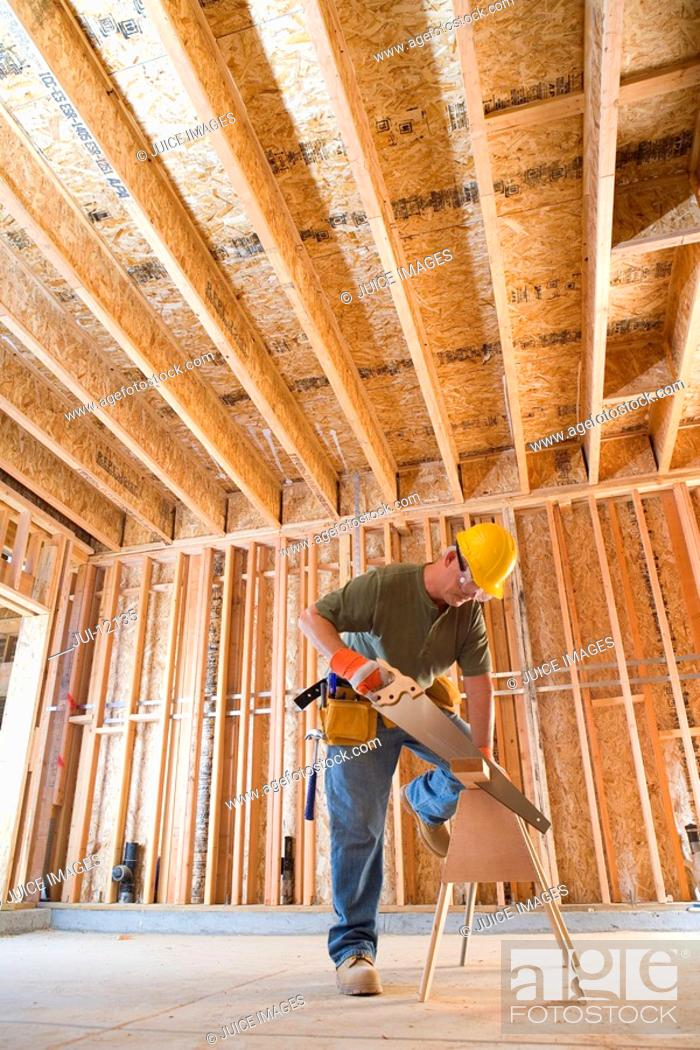 Stock Photo: Builder in hardhat sawing, low angle view.